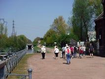 Grupp av fotgängare längs bankerna av en kanal royaltyfri bild