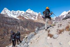 Grupp av fotvandrare som går upp på brant bergslinga royaltyfri fotografi