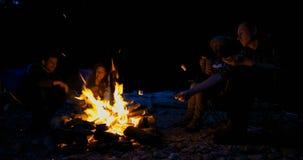 Grupp av fotvandrare som grillar marshmallower nära lägereld 4k lager videofilmer