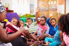 Grupp av förskole- barn som lyfter händer för att svara läraren Royaltyfri Foto
