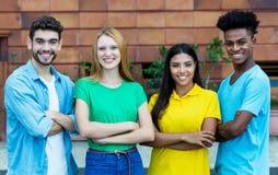 Grupp av fyra afrikansk amerikan och latin och caucasian unga vuxna m?nniskor arkivbilder
