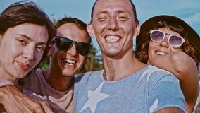 Grupp av fyra bekymmerslösa attraktiva lyckliga vänner som har roligt utomhus stående två för pelikan för kamratskap för bakgrund arkivfilmer
