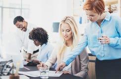 Grupp av fyra coworkers som diskuterar affärsplan i ett kontor Ungdomarsom gör stora idéer Horisontal suddig bakgrund arkivfoto