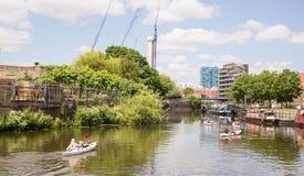 Grupp av fyra kajaker som paddlar på en kanal i östliga London Royaltyfri Bild