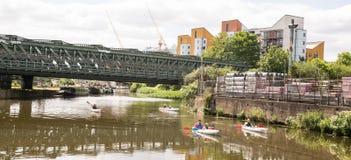 Grupp av fyra kajaker som paddlar på en kanal i östliga London Arkivbilder