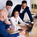 Grupp av fyra ledare som tillsammans arbetar till befordrings- idéer för kläckning av ideer Arkivfoto