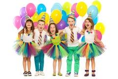 Grupp av glade små ungar som har gyckel på födelsedagen arkivfoton