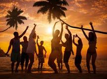 Grupp av gladlynt folk som festar på en strand Fotografering för Bildbyråer