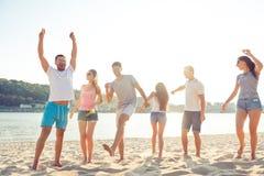 Grupp av gladlynt folk som har partiet och att dansa för strand royaltyfri foto