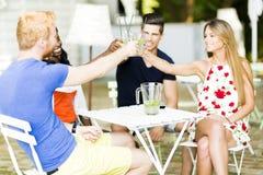 Grupp av gladlynt lyckligt folk som rostar, medan sitta på en tabell Royaltyfri Bild