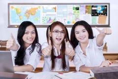 Grupp av gladlynta elever som visar upp tummar Arkivfoto