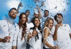 Grupp av gladlynta glade ungdomarsom tillsammans står och firar över blå bakgrund royaltyfria bilder