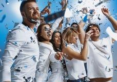 Grupp av gladlynta glade ungdomarsom tillsammans står och firar över blå bakgrund fotografering för bildbyråer