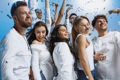 Grupp av gladlynta glade ungdomarsom tillsammans står och firar över blå bakgrund arkivfoton