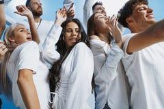 Grupp av gladlynta glade ungdomarsom tillsammans står och firar över blå bakgrund arkivfoto