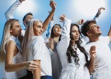 Grupp av gladlynta glade ungdomarsom tillsammans står och firar över blå bakgrund royaltyfri bild