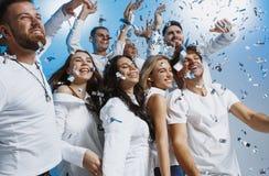 Grupp av gladlynta glade ungdomarsom tillsammans står och firar över blå bakgrund royaltyfri fotografi