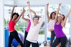 Grupp av gladlynta kvinnor som övar med lyftta armar royaltyfria foton