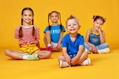 Grupp av gladlynta lyckliga barn på kulör gul bakgrund fotografering för bildbyråer