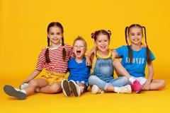 Grupp av gladlynta lyckliga barn p? kul?r gul bakgrund arkivfoto