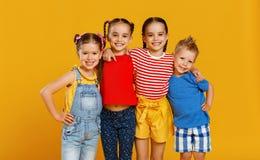 Grupp av gladlynta lyckliga barn p? kul?r gul bakgrund royaltyfria bilder