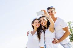 Grupp av gladlynta och härliga ungdomarsom tar foto av th Arkivfoton