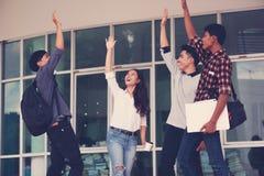 Grupp av gladlynta studenter med lyftta händer i universitetsområdet, Stu royaltyfri fotografi