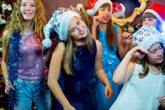 Grupp av gladlynta unga flickor som firar jul royaltyfria bilder