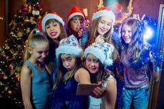 Grupp av gladlynta unga flickor som firar jul Selfie arkivfoton