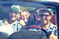 Grupp av gladlynta unga vänner som kör bilen och ler i sommar royaltyfri bild