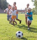 Grupp av gladlynta ungar som spelar fotboll tillsammans på grön gräsmatta I Arkivbilder