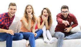 Grupp av gladlynta vänner som håller ögonen på deras favorit- film royaltyfri foto
