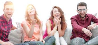 Grupp av gladlynta vänner som håller ögonen på deras favorit- film arkivfoton