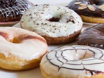 Grupp av glasade donuts på vit bakgrund Arkivfoton