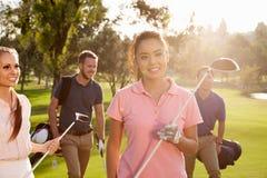 Grupp av golfare som promenerar bärande golfpåsar för farled royaltyfri foto