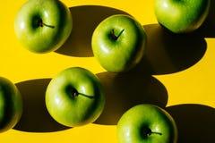 Grupp av gröna äpplen på gul bakgrund arkivfoton