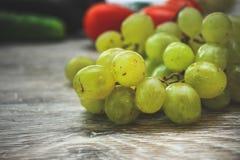 Grupp av gröna druvor på en ljus trätabletop royaltyfria bilder