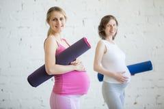Grupp av gravida konditionkvinnor som rymmer sportmats Arkivbilder