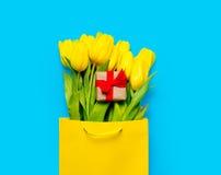 Grupp av gula tulpan och den gulliga gåvan i kall shoppingpåse på th Royaltyfri Fotografi