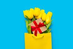 Grupp av gula tulpan och den gulliga gåvan i kall shoppingpåse på th Royaltyfri Bild