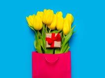 Grupp av gula tulpan och den gulliga gåvan i kall shoppingpåse på th Arkivfoto