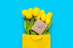Grupp av gula tulpan och den gulliga gåvan i kall shoppingpåse på th Arkivfoton
