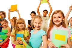 Grupp av gulliga flickor och pojkar som rymmer läroböcker Fotografering för Bildbyråer