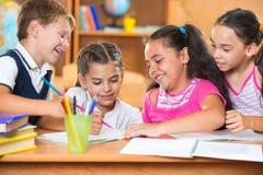 Grupp av gulliga skolbarn som har gyckel i klassrum Arkivfoton