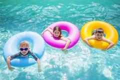 Grupp av gulliga ungar som spelar på uppblåsbara rör i en simbassäng på en solig dag Fotografering för Bildbyråer