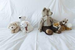 Grupp av gulliga välfyllda djur på en vit soffa Royaltyfria Foton