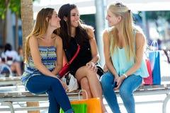Grupp av härliga unga flickor i gatan isolerar blonda blåa dagögon för påsar shopping som tar white Royaltyfri Foto