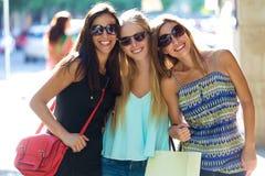 Grupp av härliga unga flickor i gatan isolerar blonda blåa dagögon för påsar shopping som tar white Arkivbilder
