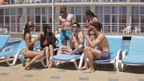 Grupp av härliga unga vänner som dricker coctailar och har roligt sammanträde av simbassängen Skjutit i 4k arkivfilmer