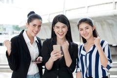 grupp av härliga vänner för unga kvinnor som använder en smart telefon och skratta upphetsande affär för tre flicka direktanslute arkivfoton